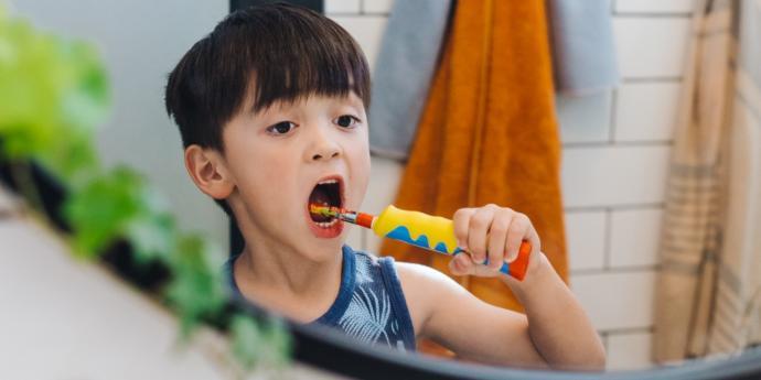 Şarjlı Diş Fırçası ile Dişlerini Fırçalayan Bir Çocuk