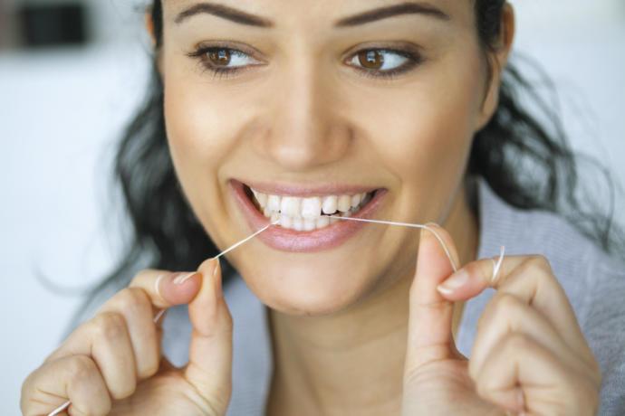 diş ipi tutan kadın
